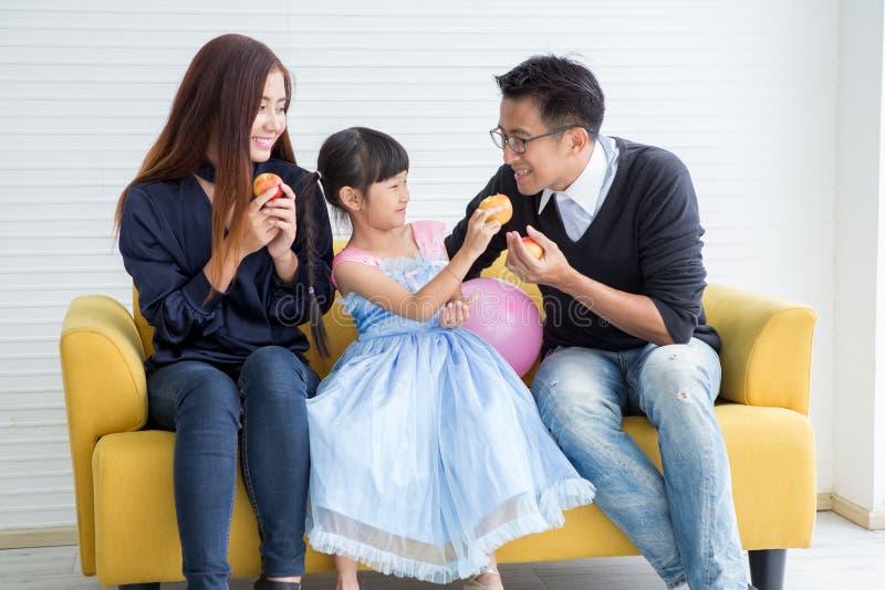 Gelukkige familie en jonge geitjes die ontbijtzitting op bank, Moeder en vader hebben die appel samen met dochterochtend eten stock afbeelding