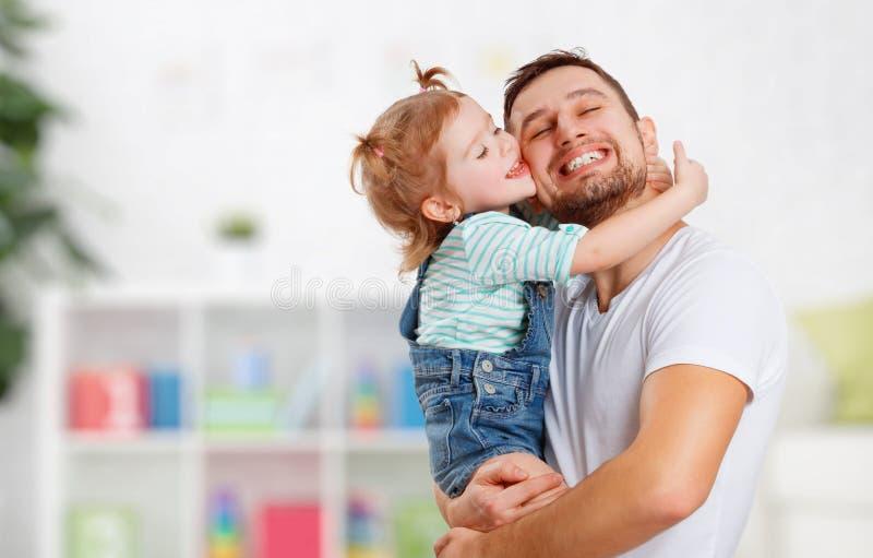 Gelukkige familie en van de vader dag Dochter die en papa kussen koesteren stock afbeelding