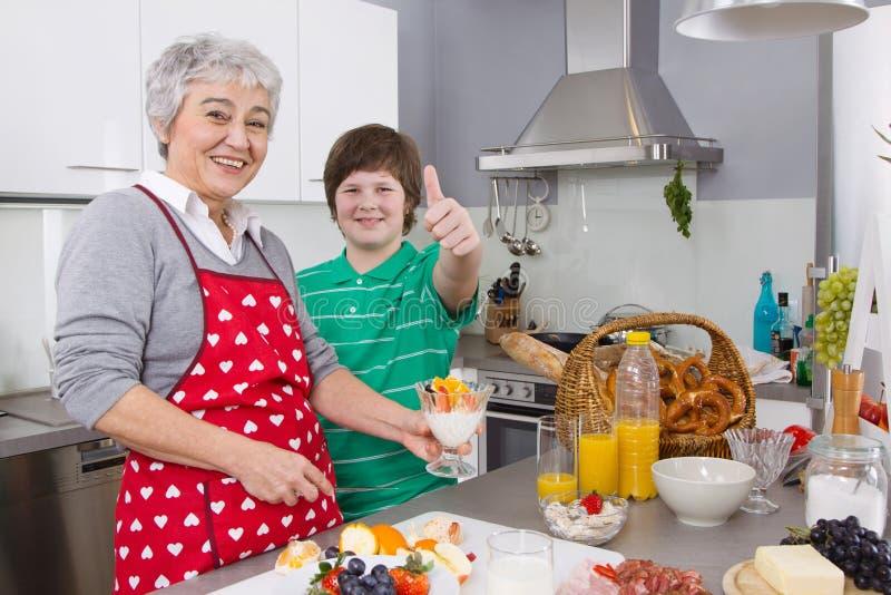 Gelukkige familie: Grootmoeder en kleinzoon die samen koken royalty-vrije stock foto