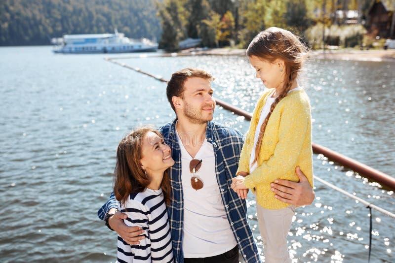 Gelukkige familie het besteden tijd samen buitenkant dichtbij meer Ouders die met dochter spelen die en pret koesteren hebben stock foto's