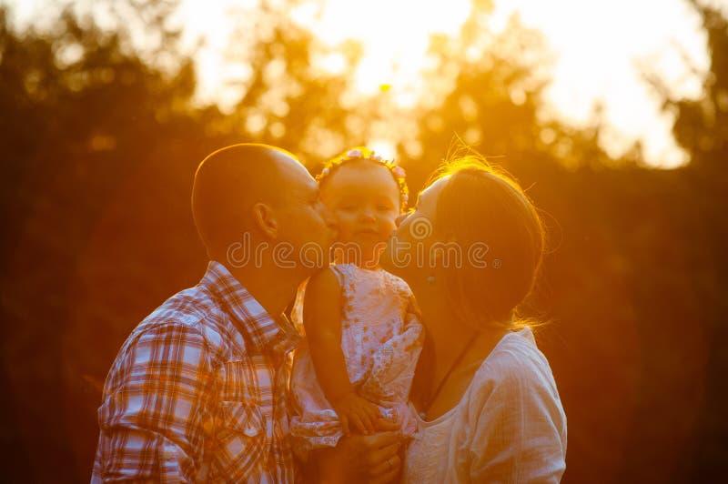 Gelukkige familie in het licht van de parkavond De lichten van een zon Mamma, papa en baby gelukkige gang bij zonsondergang Het c stock foto's