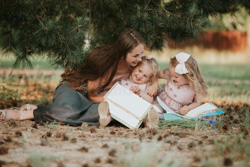 Gelukkige familie - het mamma en twee dochters zitten in een weide en lezen een boek Picknick stock afbeelding