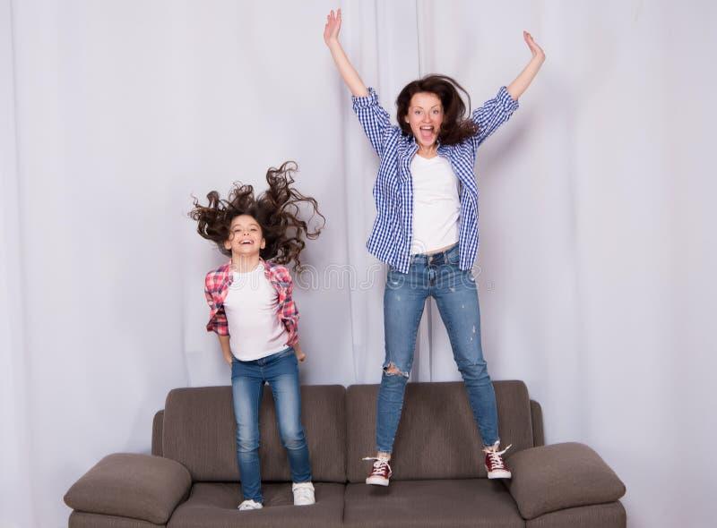 Gelukkige familie het vieren moedersdag Gelukkige moeder en dochter die op bank springen Moeder en kind die van gelukkige moeders royalty-vrije stock afbeelding