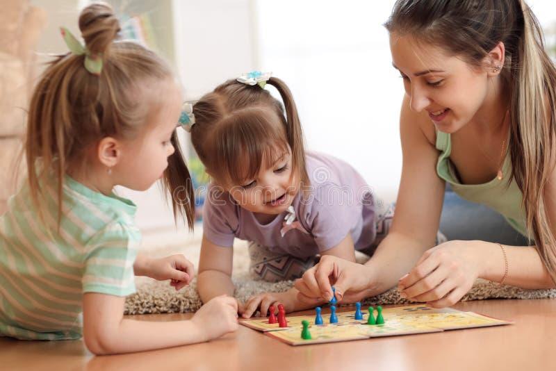 Gelukkige Familie Jonge moeder die Ludo boardgame met haar dochters spelen terwijl samen thuis het doorbrengen van tijd stock afbeelding