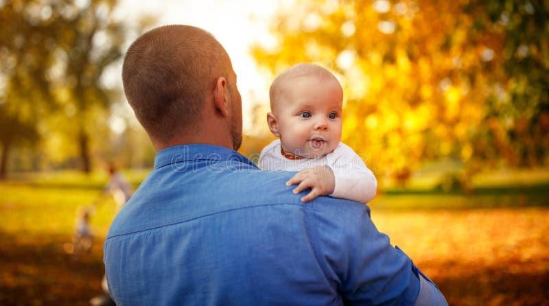 Gelukkige familie - Jonge vader en babyjongen in de herfstpark stock afbeeldingen