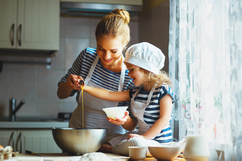 Gelukkige Familie in Keuken moeder en het kind die deeg de voorbereiden, bakken stock foto's