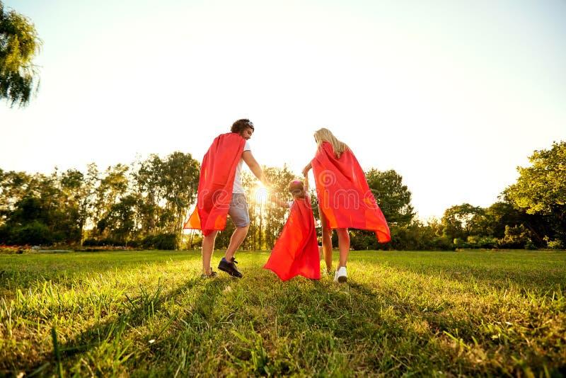 Gelukkige familie in kostuums van superheroes in het park bij zonsondergang royalty-vrije stock afbeeldingen