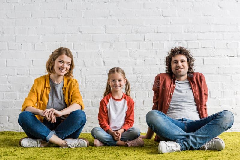gelukkige familie met één kind die bij camera glimlachen terwijl samen het zitten royalty-vrije stock afbeelding