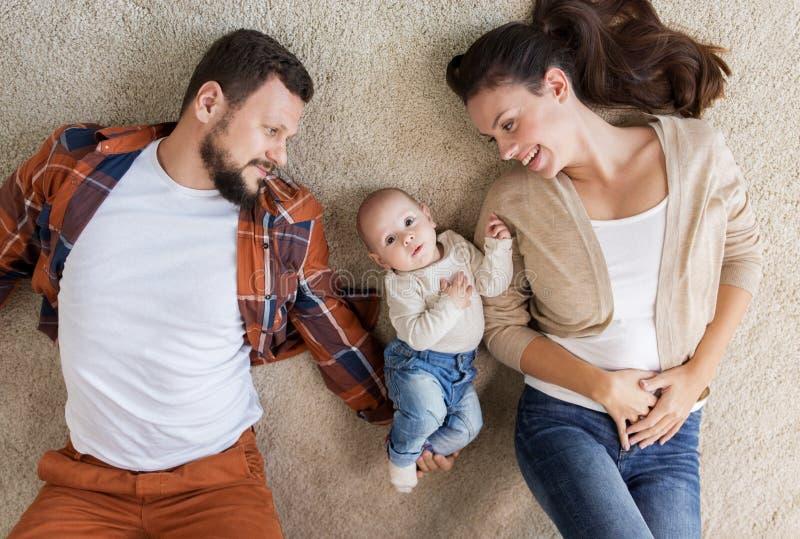 Gelukkige familie met baby het liggen op vloer thuis royalty-vrije stock afbeelding