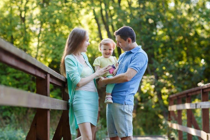 Gelukkige familie met baby in park op brug stock afbeelding
