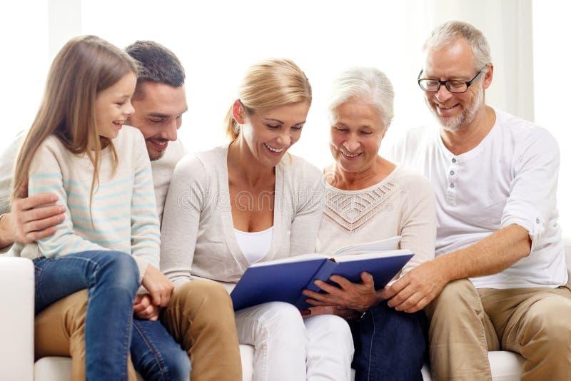 Gelukkige familie met boek of fotoalbum thuis royalty-vrije stock afbeelding