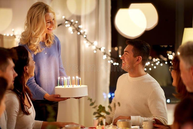 gelukkige familie met cake die verjaardagspartij hebben stock afbeelding