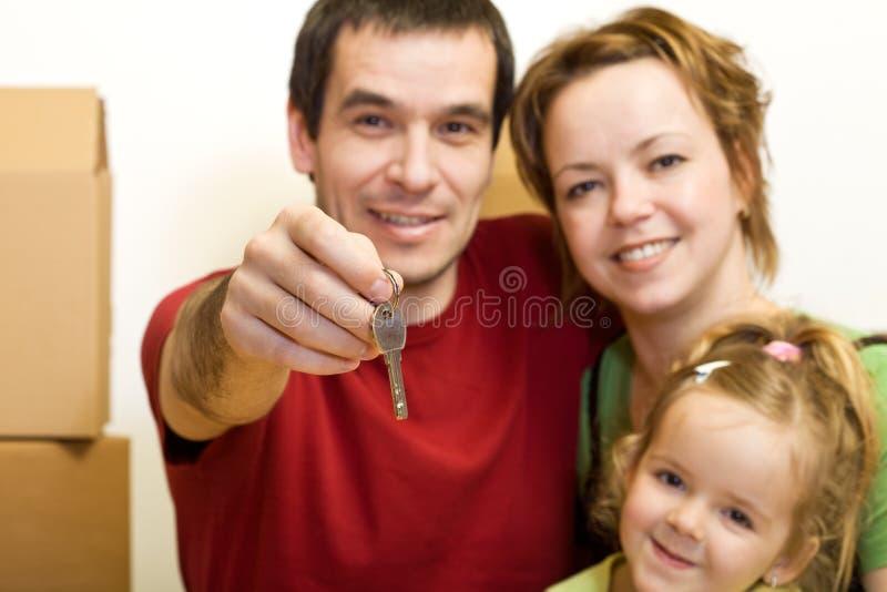 Gelukkige familie met de sleutel van hun nieuw huis royalty-vrije stock foto's