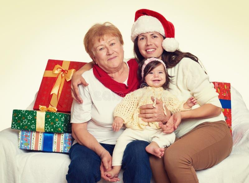 Gelukkige familie met doosgift, vrouw met kind en bejaarden - vakantieconcept stock afbeelding