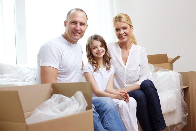 Gelukkige familie met dozen die zich aan nieuw huis bewegen stock afbeeldingen