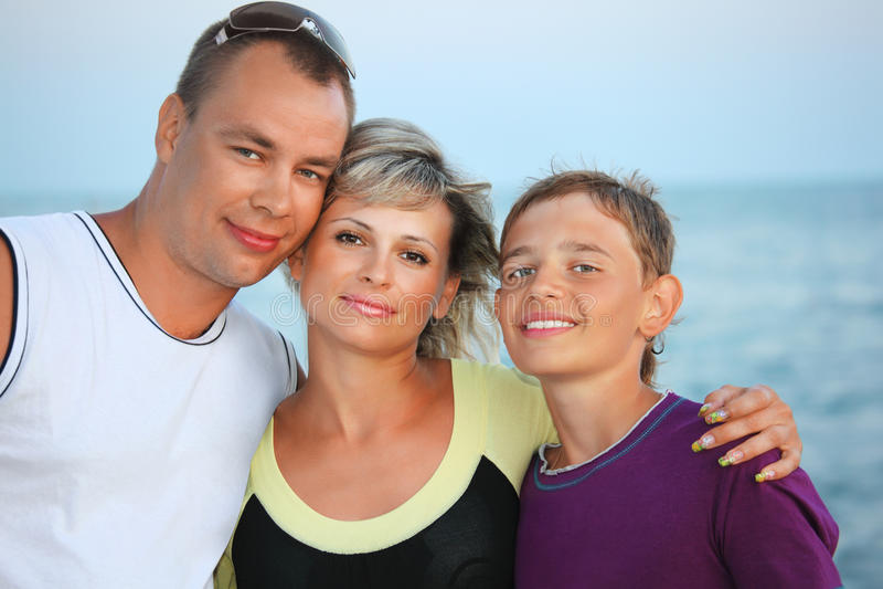Gelukkige familie met glimlachende jongen op strand in avond royalty-vrije stock afbeelding