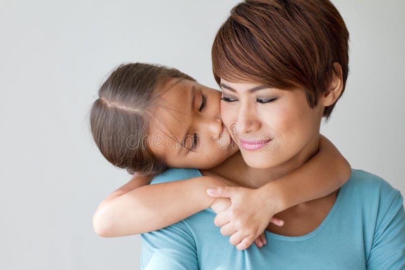 Gelukkige familie met het glimlachen, positieve dochter die haar mother kussen royalty-vrije stock fotografie