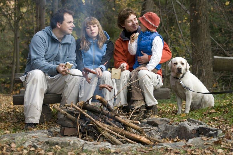Gelukkige familie met hond dichtbij kampvuur royalty-vrije stock foto's
