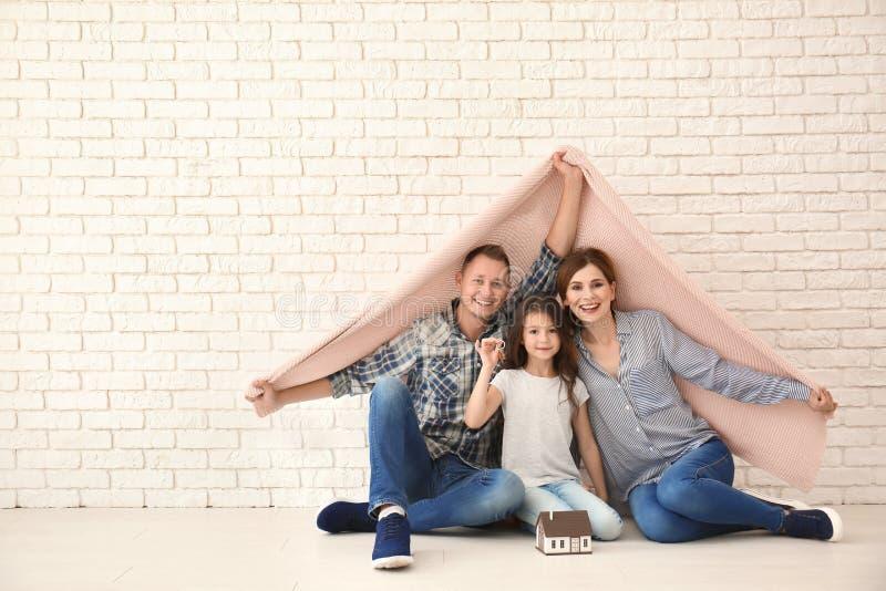 Gelukkige familie met huismodel en sleutel van hun nieuw huis onder plaid binnen royalty-vrije stock afbeeldingen
