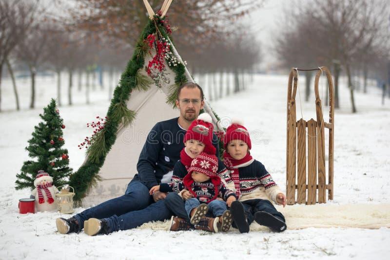Gelukkige familie met jonge geitjes, die pret openlucht in de sneeuw op Christus hebben royalty-vrije stock afbeeldingen