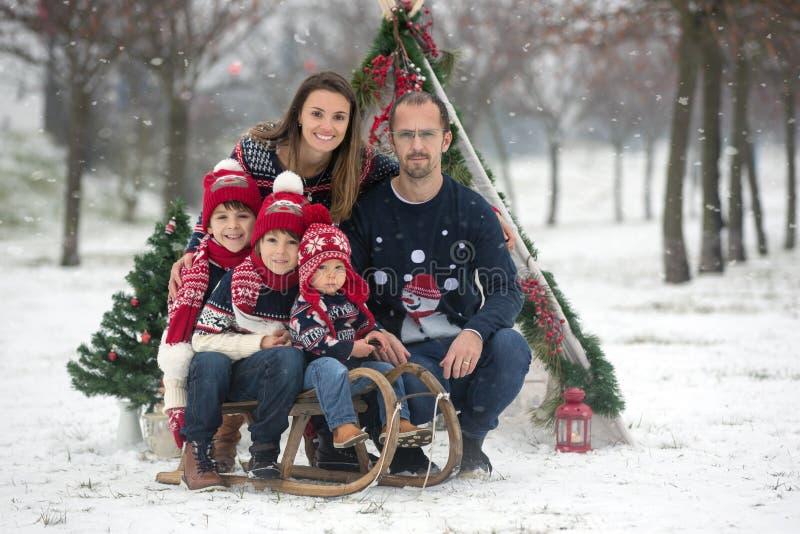 Gelukkige familie met jonge geitjes, die pret openlucht in de sneeuw op Christus hebben stock foto's