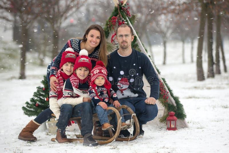 Gelukkige familie met jonge geitjes, die pret openlucht in de sneeuw op Christus hebben royalty-vrije stock afbeelding