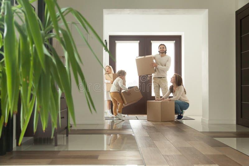 Gelukkige familie met jonge geitjes dozen houden die zich beweegt in nieuw huis royalty-vrije stock afbeeldingen