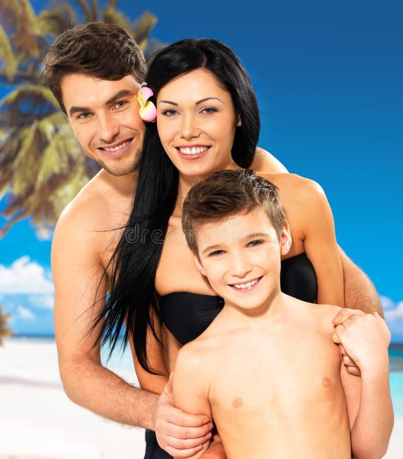 Gelukkige familie met kind bij tropisch strand stock fotografie