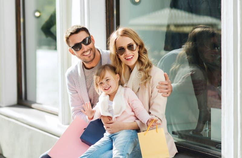 Gelukkige familie met kind en het winkelen zakken in stad royalty-vrije stock foto