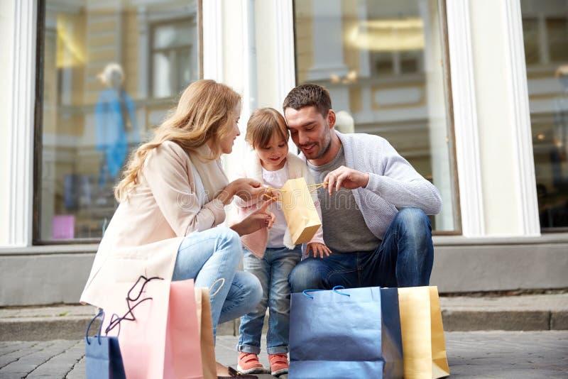 Gelukkige familie met kind en het winkelen zakken in stad royalty-vrije stock afbeelding