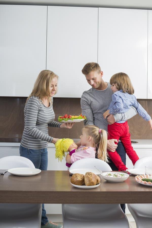 Gelukkige familie met kinderen die maaltijd in binnenlandse keuken hebben stock foto's