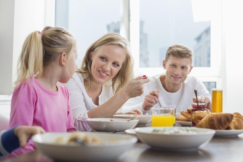 Gelukkige familie met kinderen die ontbijt hebben bij lijst stock fotografie