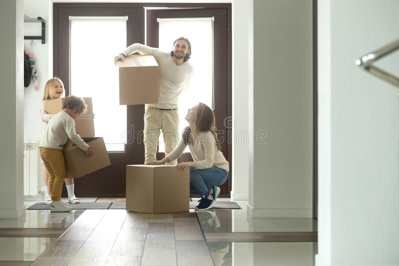 Gelukkige familie met kinderen en dozen die zich in nieuw huis bewegen stock fotografie