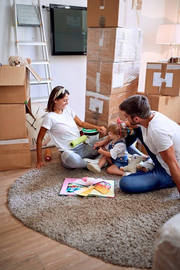 Gelukkige familie met kindmeisje in nieuw huis stock fotografie