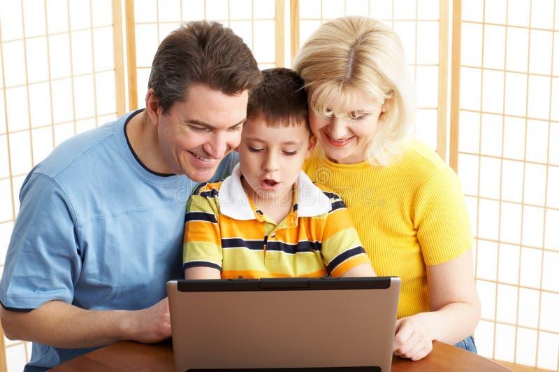 Gelukkige familie met laptop stock fotografie