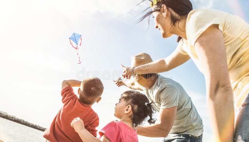 Gelukkige familie met ouders en kinderen die samen met vlieger spelen stock foto's