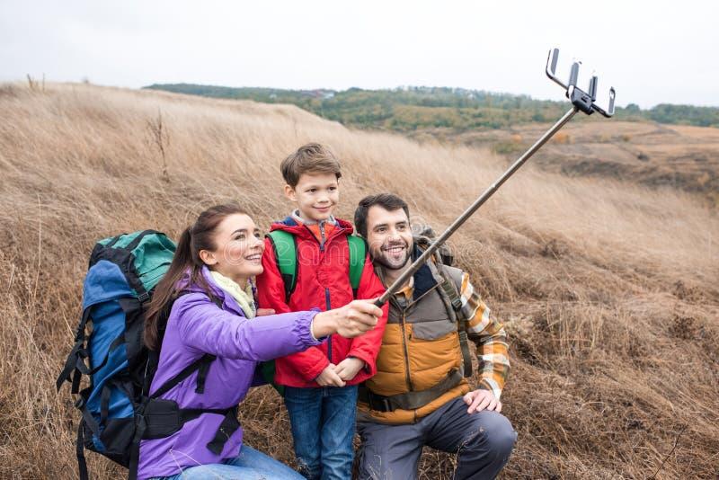 Gelukkige familie met rugzakken die selfie nemen stock fotografie
