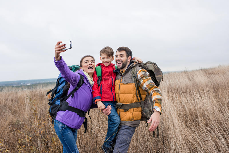 Gelukkige familie met rugzakken die selfie nemen stock afbeeldingen
