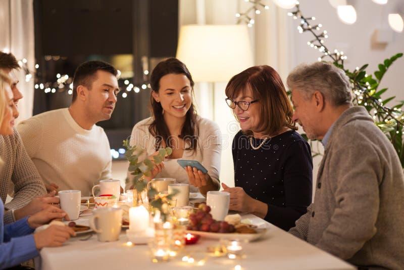 Gelukkige familie met smartphone bij theekransje thuis stock afbeeldingen