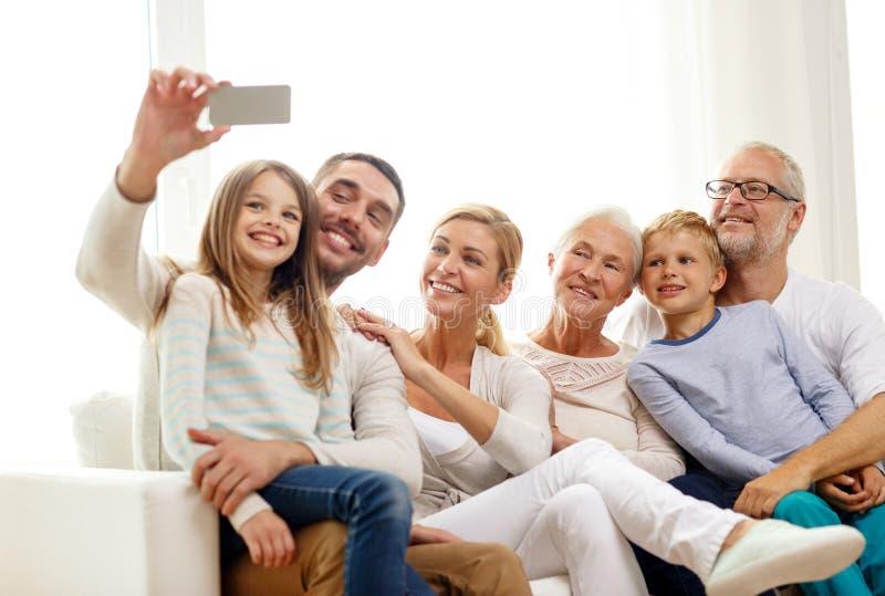 Gelukkige familie met smartphone thuis stock afbeeldingen