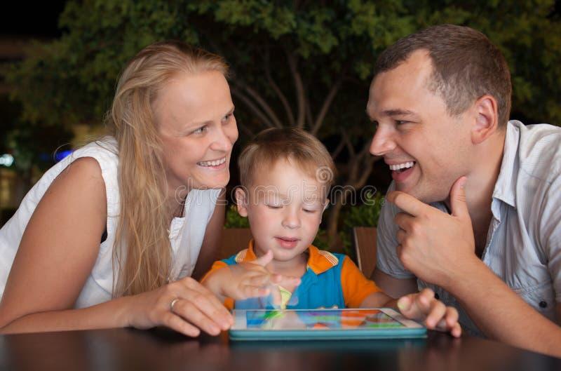 Gelukkige familie met tabletpc openlucht in de avond stock foto's