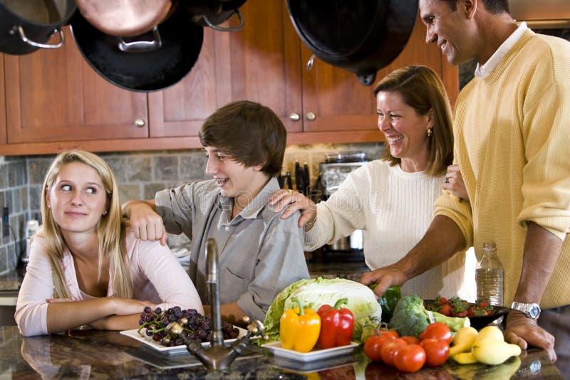 Gelukkige familie met tieners die in keuken glimlachen stock afbeeldingen