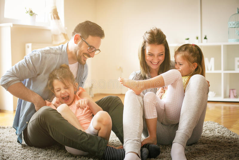 Gelukkige familie met twee dochters die thuis spelen stock fotografie