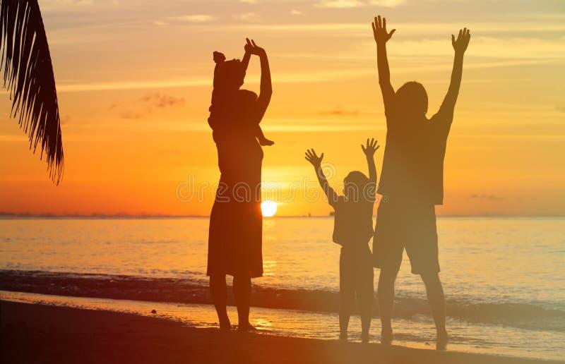 Gelukkige familie met twee jonge geitjes die pret hebben bij zonsondergang stock foto
