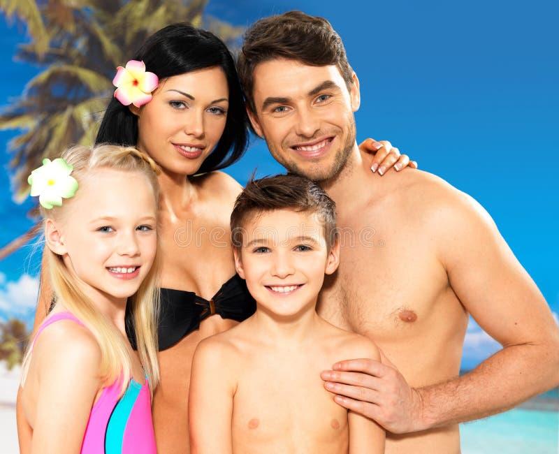 Gelukkige familie met twee kinderen bij tropisch strand royalty-vrije stock afbeelding