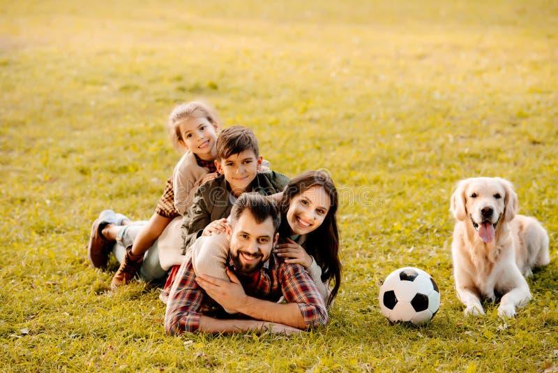 Gelukkige familie met twee kinderen die in een stapel op gras met hondzitting liggen stock afbeelding