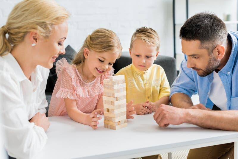 gelukkige familie met twee kinderen die met houten blokken thuis spelen stock foto's