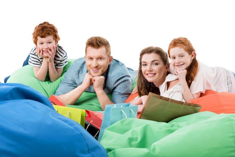 gelukkige familie met twee kinderen die op kinderspelstoelen rusten en bij camera na het winkelen glimlachen royalty-vrije stock afbeeldingen