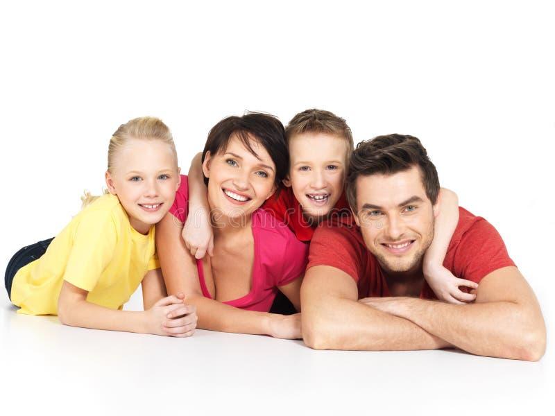 Gelukkige familie met twee kinderen die op witte vloer liggen stock foto