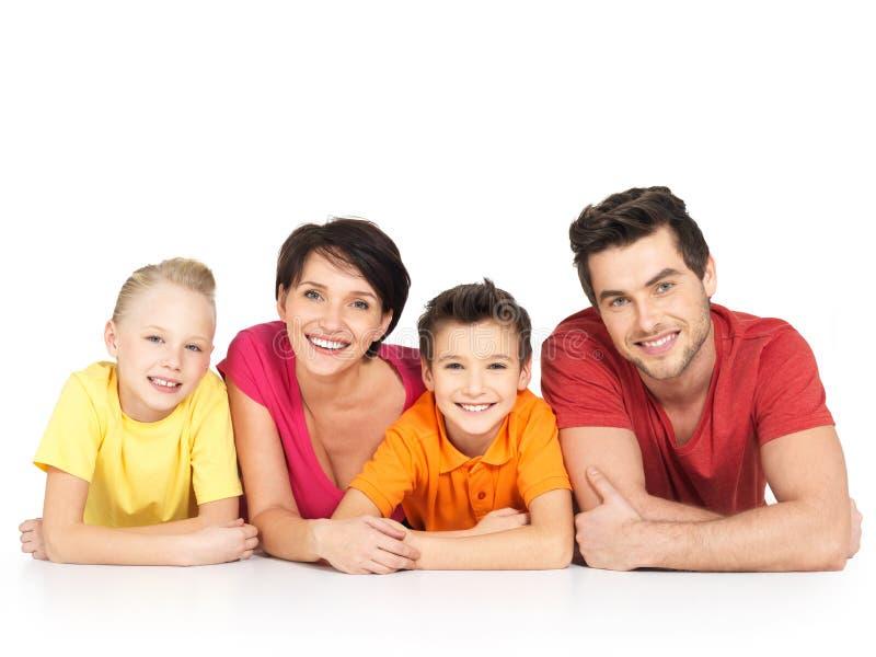Gelukkige familie met twee kinderen die op witte vloer liggen